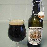 Kozarec s pivom na levi strani in odprta steklenica piva na desni strani
