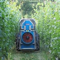 Pršilnik v vinogradu med vrstama pri nanašanju fungicidov.